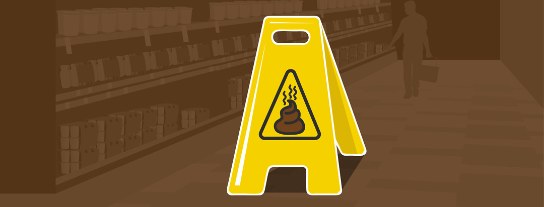 A stand up caution sign is positioned in the middle of a store aisle, showing the poop emoji in the center of the warning triangle.