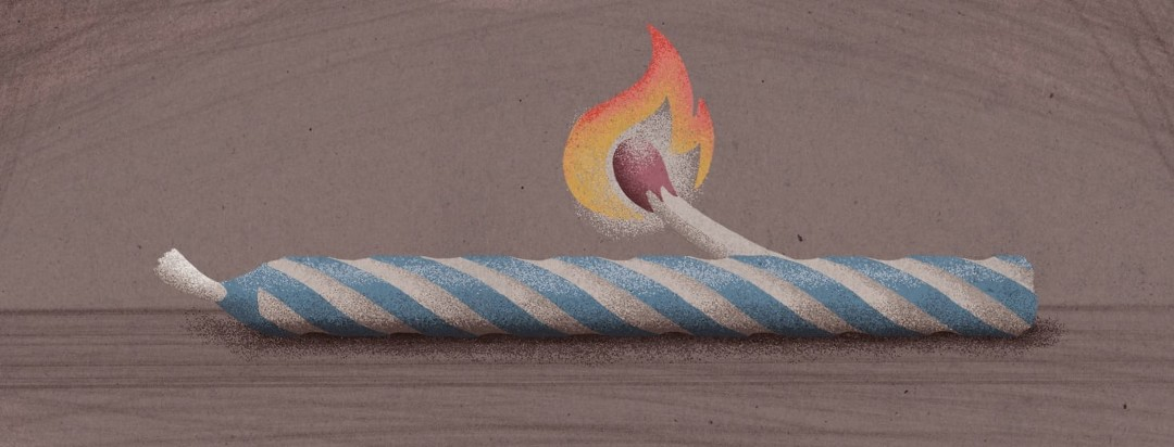 An unburnt birthday candle laying on its side while a burning match hovers above the middle.