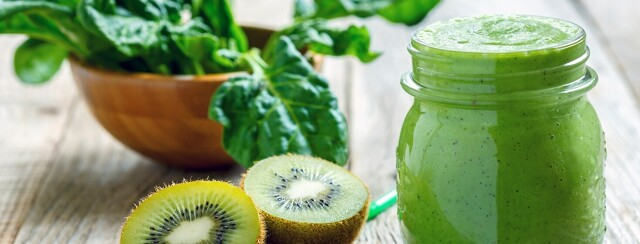 Green smoothie in a glass jar surrounded by a bowl of spinach and a kiwi.