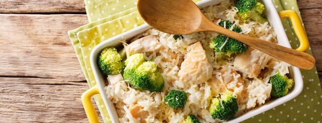Chicken and rice in a casserole dish with a wooden spoon across the corner.
