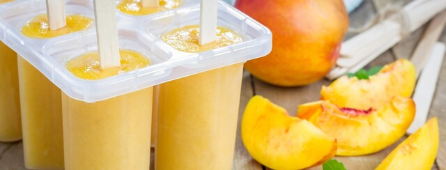 Peach puree in an ice pop mold surrounded by sliced peaches.