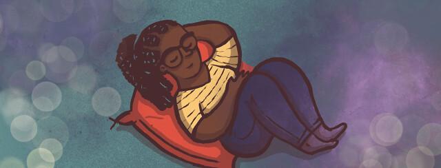 A woman curled up peacefully on a floor cushion.