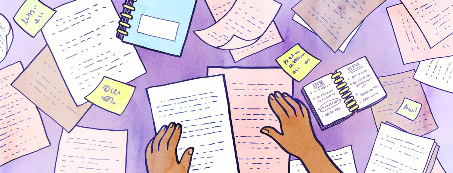 Hands spread out many papers on a flat surface.